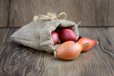 Dry bulb onions for planting in a small sack on wooden backgroun