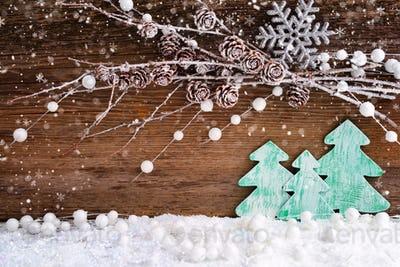 Christmas card with wooden christmas trees on the snow on a wood