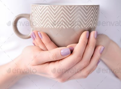Hands of a young woman holding a cup of tea