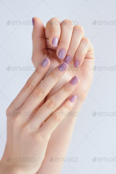 Closeup of hands of a young woman with pink manicure on nails