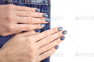 Female hands with dark blue manicured nails with jeans on white