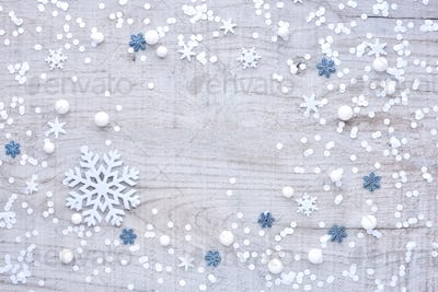 Snowflakes and confetti on a light wooden background. Festive Ch