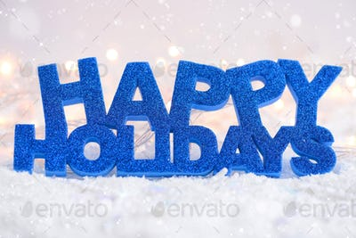 """Greeting """"Happy Holidays"""" is on snow on a festive background"""