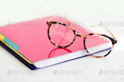 Eye glasses with pink spiral notebook on white background