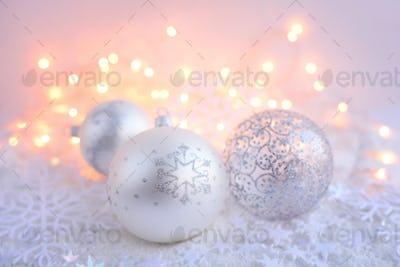 Christmas decorative balls on snow and Christmas lights. Festive