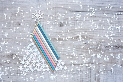 Christmas tree made of pencils and snowflakes on a light wooden
