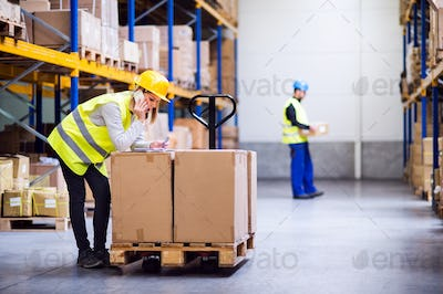 Young warehouse workers with smartphone.