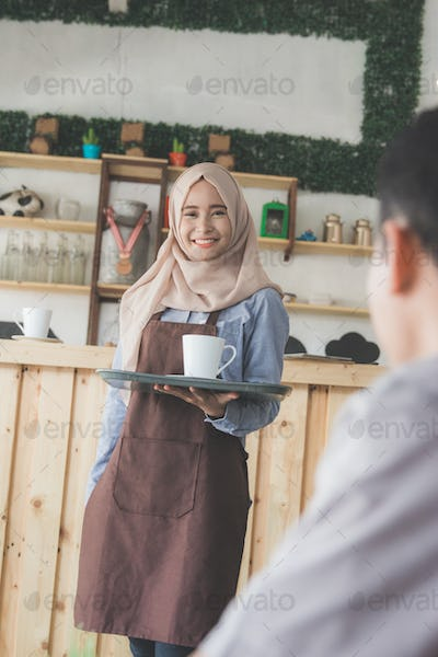 female waitress serving coffe at the cafe