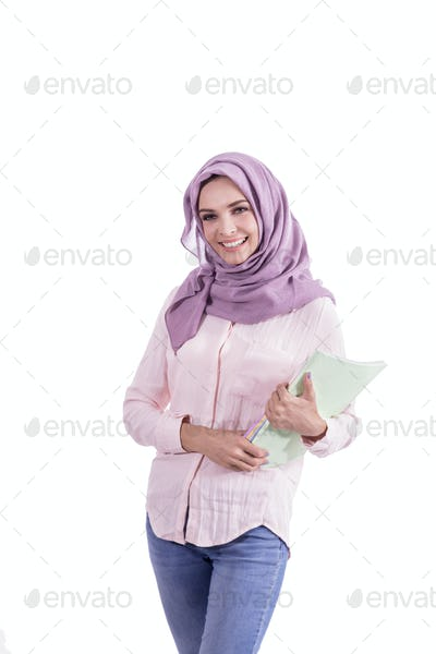 beautiful college student wearing hijab smiling while bringing s