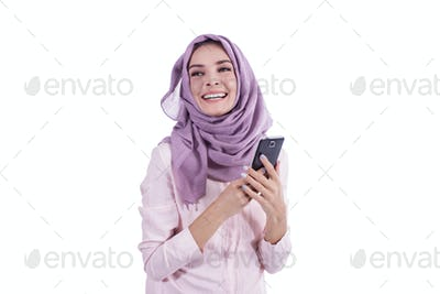 beautiful happy woman wearing hijab smiling while holding mobile
