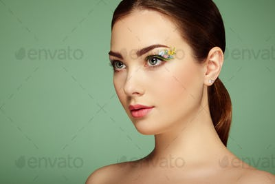 Young beautiful woman with flower makeup eyes
