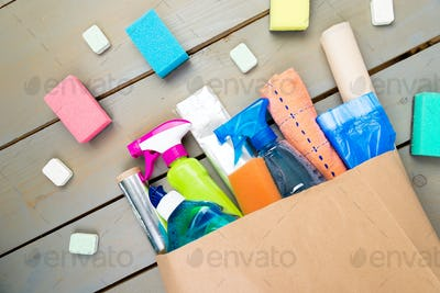 Full paper bag of different house cleaning product on wooden table.