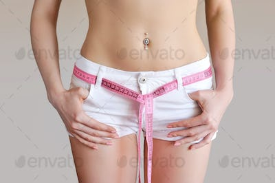 Woman measuring waist with tape on knot, dieting concept.