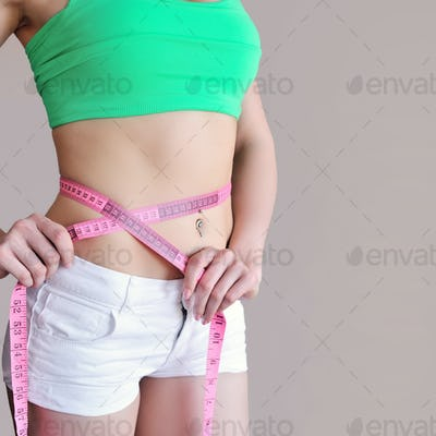 Close up of female hands measuring waist with measuring tape, di