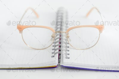 Eye glasses with opened blank spiral notebook on white backgroun