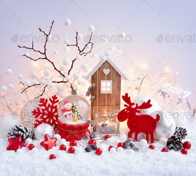 A snow globe with snowman with christmas decorations and toy hou