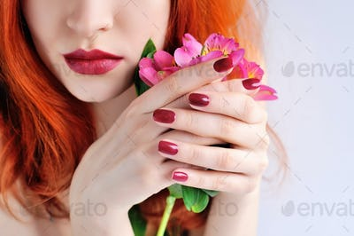 Beautiful red-haired young woman with flowers alstroemeria. Focu