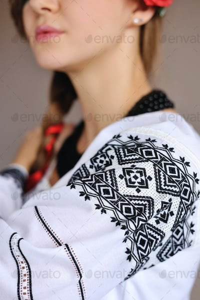 The girl in an embroidered shirt. Closeup pattern on the sleeve.