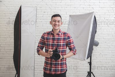 young photographer in studio with lighting at the beackground