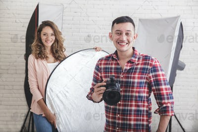 young photographer with his beautiful assistant in studio