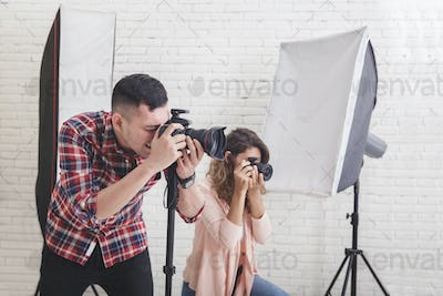 two young photographers in action taking a photo