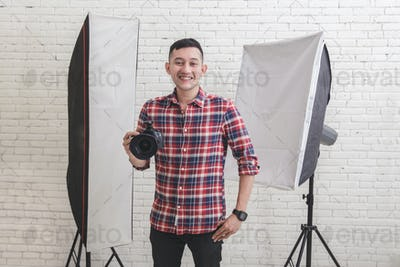 Young smiling photographer with camera in professionally equippe
