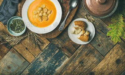 Fall pumpkin cream soup with croutons and seeds, flat-lay