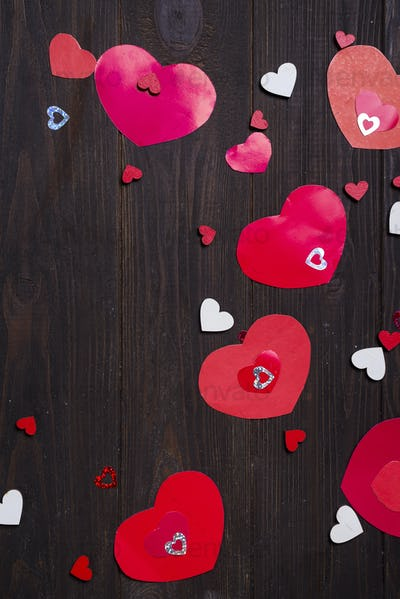 Red paper hearts on wooden background.