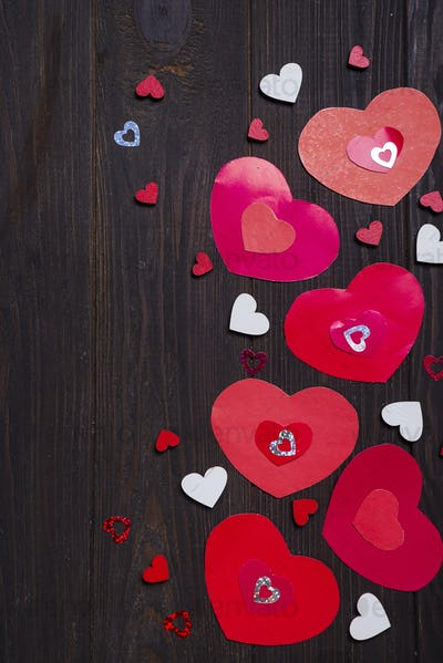 Border of Red paper hearts on wooden background.