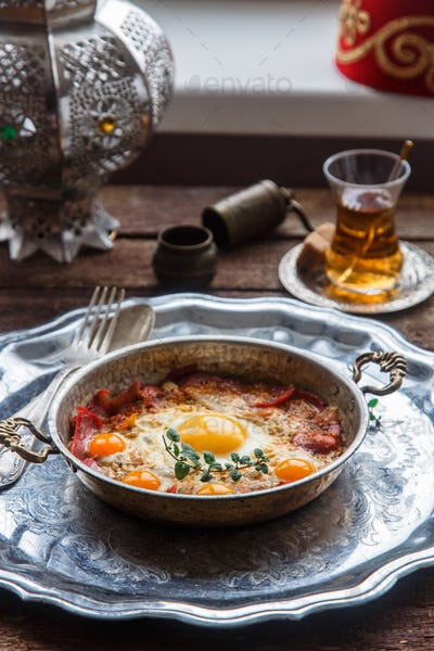 Copper pan with fried eggs and sausages, turkish style