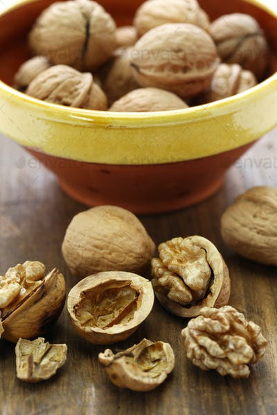 walnuts, kernel and shell on wooden background