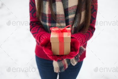A girl holding a gift in her hands on the street in winter