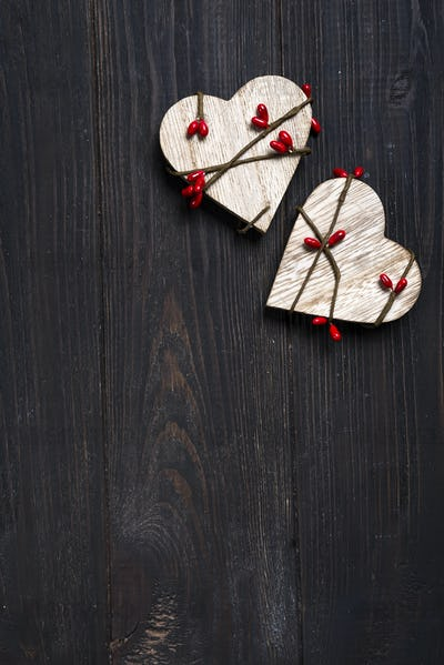 two wooden hearts on wooden background.