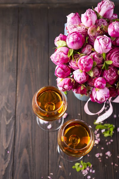 Buds of red roses and glases of wine