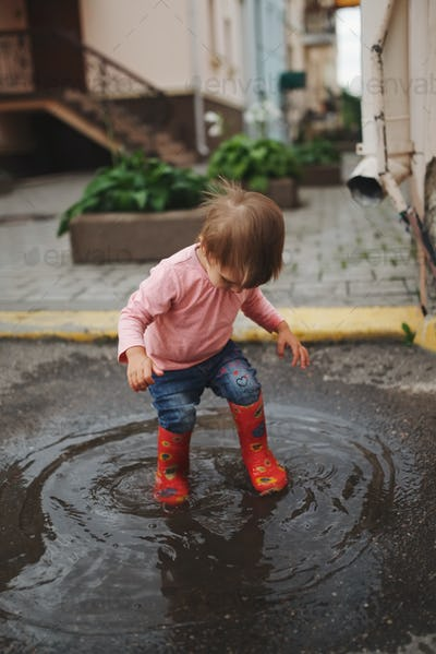 girl plays in the puddle outdoors