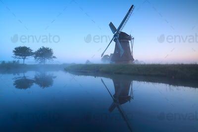 Dutch windmill by lake in dusk