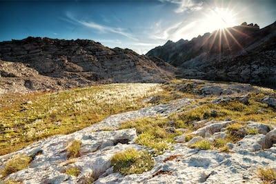 sunshine over alpinr lake between rocks