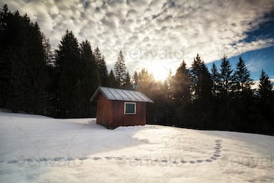 morning sunrise over cabin in winter alpine forest