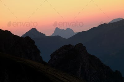 mountain silhouettes over sky at sunrise