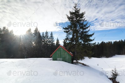 sunshine over snowy hill and wooden cabin