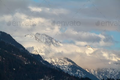 snowy mountain peaks in clouds