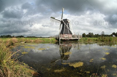 windmill reflected in lake water