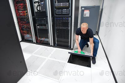 Technician Lifting Floor Tile Using Vacuum Suction Cups In Datac