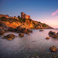 Talamone rock beach and medieval fortress at sunset. Maremma Arg