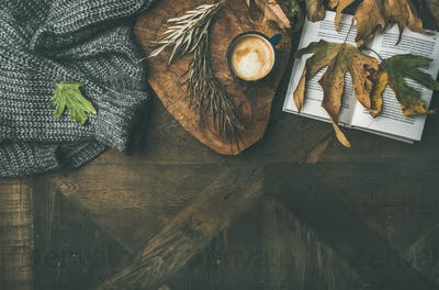 Autumn morning coffee concept with leaves, jamper and book