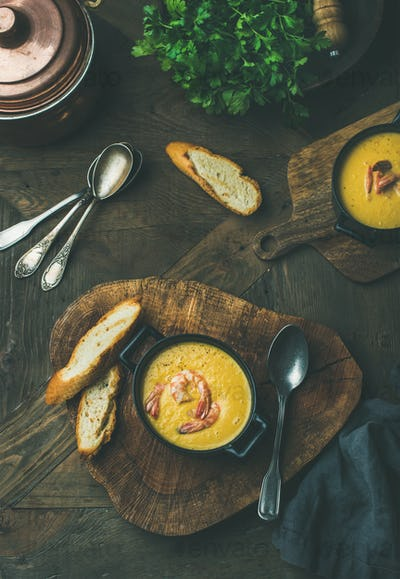 Flat-lay of corn creamy soup with shrimps, top view