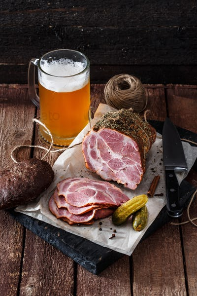 Smoked ham with rye bread, pickles and beer, rustic style