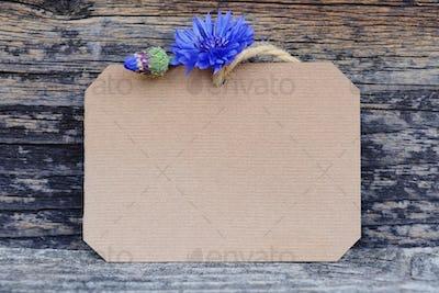 Paper tag with fresh cornflowers (Centaurea cyanus) on wooden ta