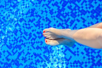 Woman feet in swimming pool on a hot summer day
