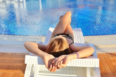Sexy young woman lying on a lounger near swimming pool with blue